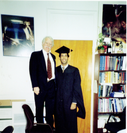 Dr. Jerry Cuomo standing on a chair with Vinay Sakhrani graduating from his Master's Degree at NCSU Materials Science Department